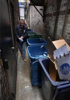 John Meaney inspected a Winter Street alley where trash bins could impede escape routes.